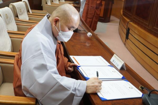 협약서에 사인하고 있는 민추본 본부장 월우 스님.
